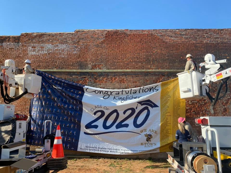 Cimarron hanging congratulatory banner for 2020 Kingisher seniors