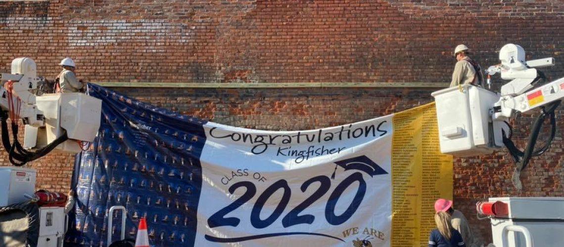 Cimarron hanging congratulatory banner for 2020 Kingisher seniors