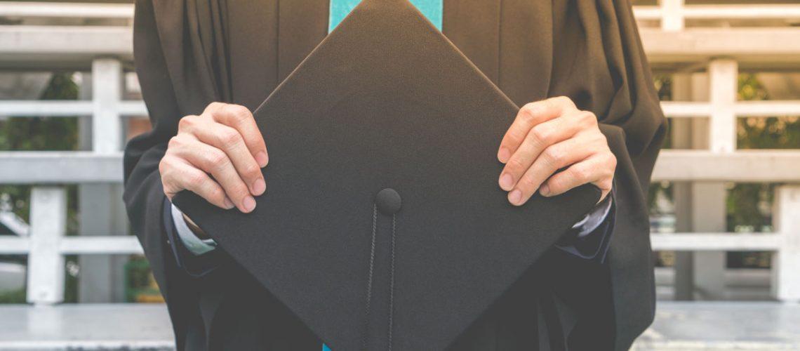 Graduate holding a cap.